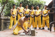 Vietnam, Hanoi, men exercising kung fu, man slabs flagstone - WPEF00538