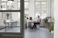 Man working at desk in a loft office - FKF02948