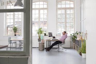 Man working at desk in a loft office - FKF02966