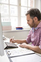 Man working at desk in office drawing on tablet - FKF02972