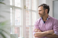 Portrait of a man looking out of window in office - FKF02975