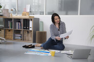 Casual woman with plans and laptop sitting on the floor in a loft office - FKF02993