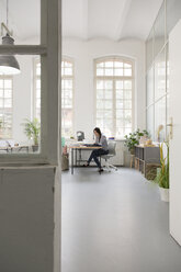 Woman working at desk in a loft office - FKF03008