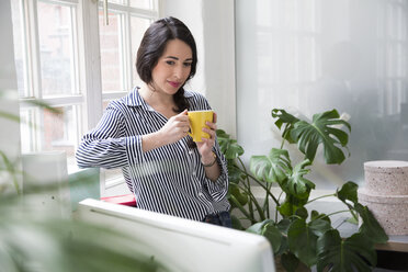 Smiling woman with cup of coffee at the window in office - FKF03026