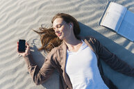 Overhead view of mid adult woman lying in sand listening to earphones, Sardinia, Italy - CUF37465