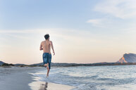 Rear view of mid adult man running on beach, Sardinia, Italy - CUF37468