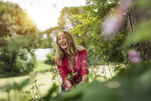 Young woman laughing whilst cutting flowers in garden - CUF37474
