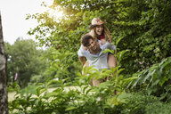 Young man giving girlfriend a piggy back in garden - CUF37480
