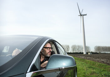 Man in car with wind turbine in background - CUF37483