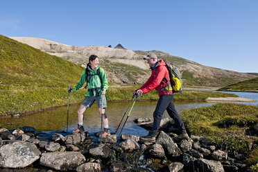 Mature hiking couple crossing river with walking sticks, Breidvik, Borgafjordur East, East Iceland - CUF37504