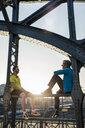 Friends relaxing on bridge, Munich, Bavaria, Germany - CUF37507