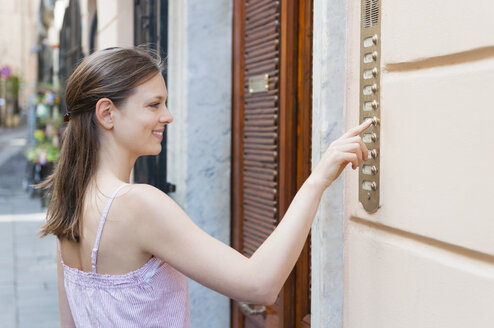 Mid adult woman pressing holiday apartment doorbell, Sardinia, Italy - CUF37555