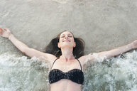 Mid adult woman lying in sea with arms open and eyes closed, Sardinia, Italy - CUF37573
