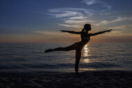 Silhouetted young woman practicing yoga pose on beach at sunset, Oristano, Sardinia, Italy - CUF37582