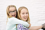 Two sisters playing piggyback - CUF37603