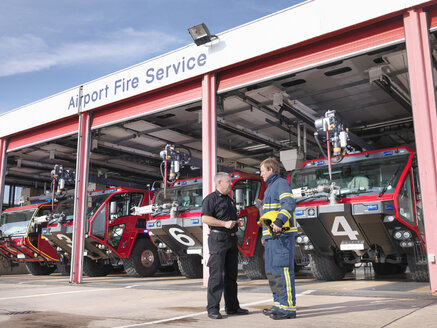 Officer and fireman in front of fire engines in airport fire station - CUF37630