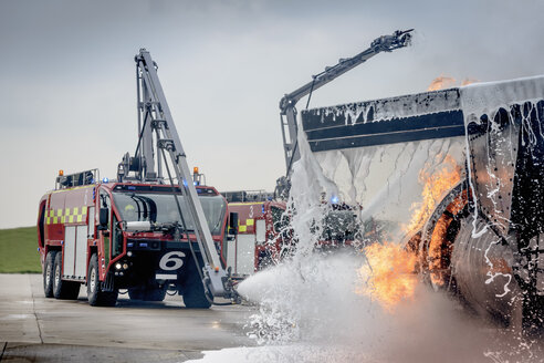 Fire engine spraying water on simulated fire at airport training facility - CUF37636