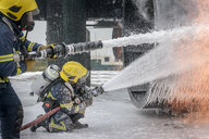 Firemen spraying water on simulated aircraft fire at training facility - CUF37639