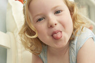 Portrait of girl lying on seat sticking tongue out - CUF37651