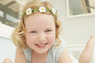 Portrait of girl in daisy chain lying on holiday apartment seat - CUF37654