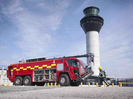 Fireman carrying equipment to fire engine in airport fire station - CUF37693