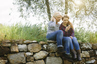 Mother and teenage daughter looking at smartphone on dry stone wall - CUF37705