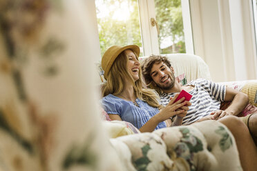 Young couple reading message on smartphone in living room - CUF37735