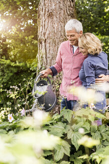 Husband and wife watering plants in garden - CUF37750