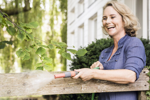 Mature woman playing with hosepipe in garden - CUF37753