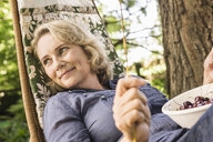 Mature woman relaxing with bowl of cherries on hammock - CUF37762