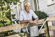 Mature man with watering can in garden - CUF37768