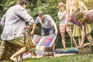 Friend preparing for picnic in garden - CUF37774