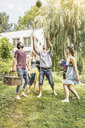 Friends playing catch with watermelon in garden - CUF37783