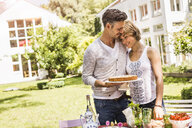 Couple in garden having tender moment, man holding cake - CUF37807