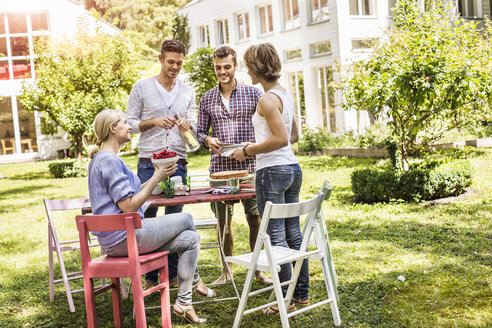 Group of friends setting up garden party - CUF37810
