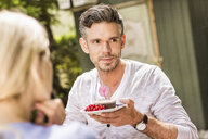 Mid adult man in garden, holding plate with cake on - CUF37822