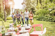 Group of friends enjoying garden party - CUF37828