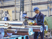 Engineer inspecting finished steel rollers in engineering factory - CUF37843