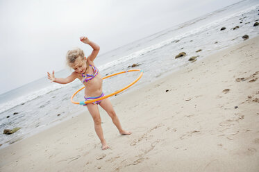 Young girl with hoolahoop on the beach - ISF14576
