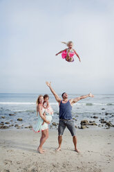 Parents and two young girls fooling around on beach - ISF14579