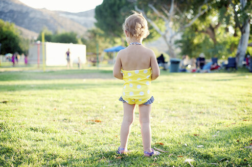 Rear view of female toddler standing in park field - ISF14603