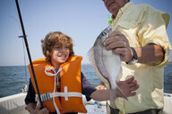 Boy and grandfather with caught fish on boat,  Falmouth, Massachusetts, USA - ISF14652