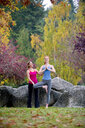 Yoga instructor teaching young woman in forest - ISF14750