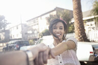Young woman holding boyfriends hand on suburban street - ISF14762