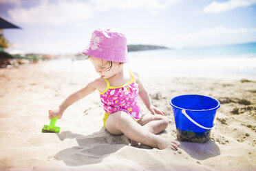 Baby playing on sandy beach with bucket and spade - ISF14903