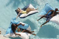 Three young adults reclining on airbeds in swimming pool, Providenciales, Turks and Caicos Islands, Caribbean - ISF15086
