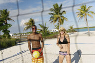 Two young adult friends playing beach volleyball, Providenciales, Turks and Caicos Islands, Caribbean - ISF15089