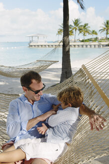 Father and son relaxing in beach hammock, Providenciales, Turks and Caicos Islands, Caribbean - ISF15101