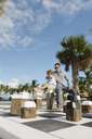 Father and son sitting on giant chess set, Providenciales, Turks and Caicos Islands, Caribbean - ISF15107