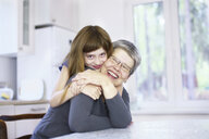 Portrait of girl hugging grandmother at kitchen table - CUF37929